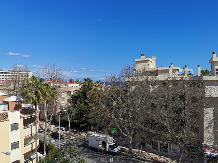 High angle view of buildings against clear blue sky