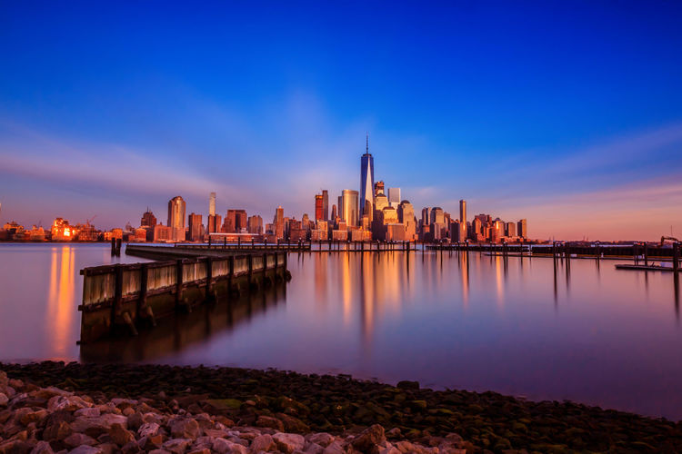 A view of the New York City skyline from Hoboken, New Jersey waterfront. Architecture Building Exterior Built Structure City Cityscape Freedom Tower Golden Hour Horizon Over Water Illuminated Modern Nature No People Outdoors Reflection Sky Skyscraper Sunset Travel Destinations Urban Skyline Water Waterfront