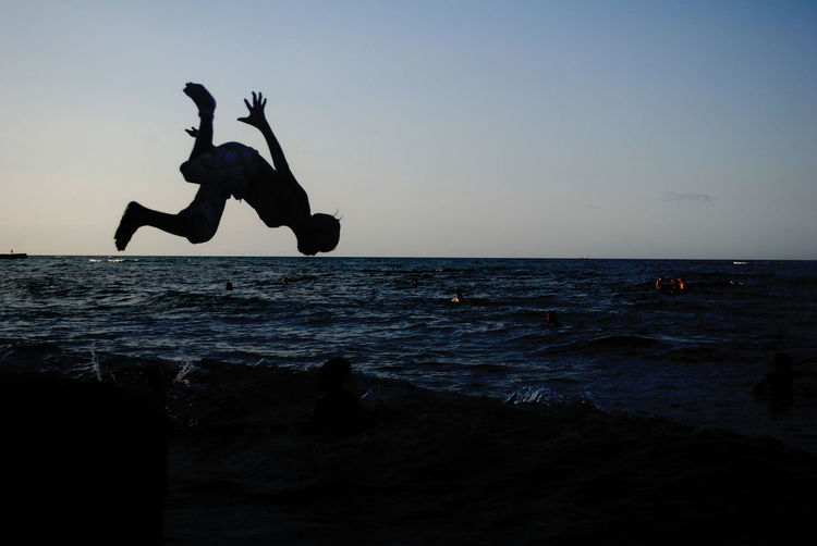 Silhouette boy jumping on beach