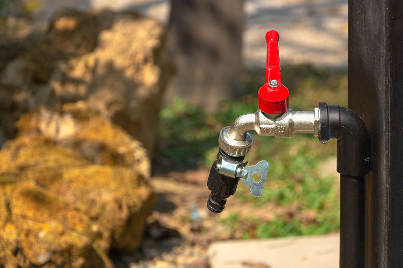 red water tap in nature background Focus On Foreground Red Faucet Metal Day No People Close-up Outdoors Pipe - Tube Nature Water Sunlight Connection Valve Tap Safety Control Pipe Security Machine Valve