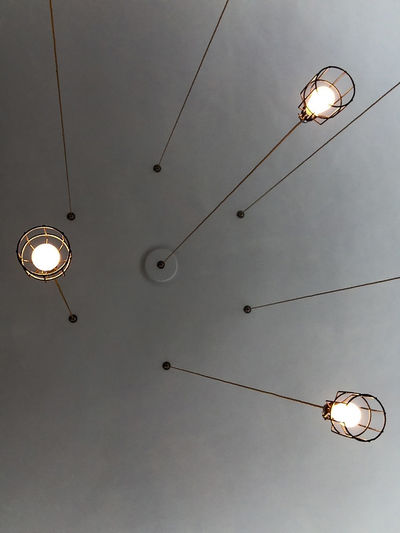 three lamps hanging from a ceiling looking upwards Ceiling Connection Decoration Electric Lamp Electric Light Electricity  Fuel And Power Generation Hanging Hanging Light Illuminated Indoor Lighting Light Bulb Lighting Lighting Equipment Low Angle View No People Power Line  Power Supply Street Light