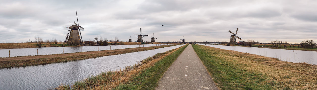 Panoramic view of canal amidst field against sky