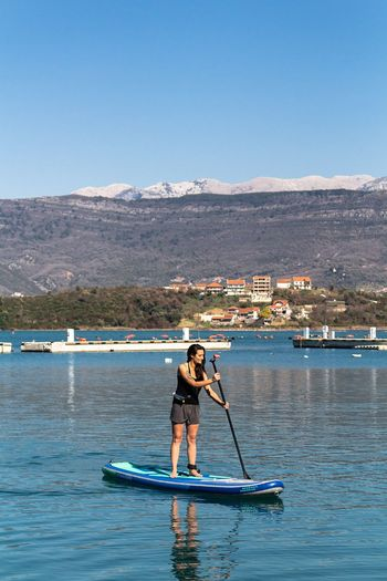 Young woman paddleboarding on sea
