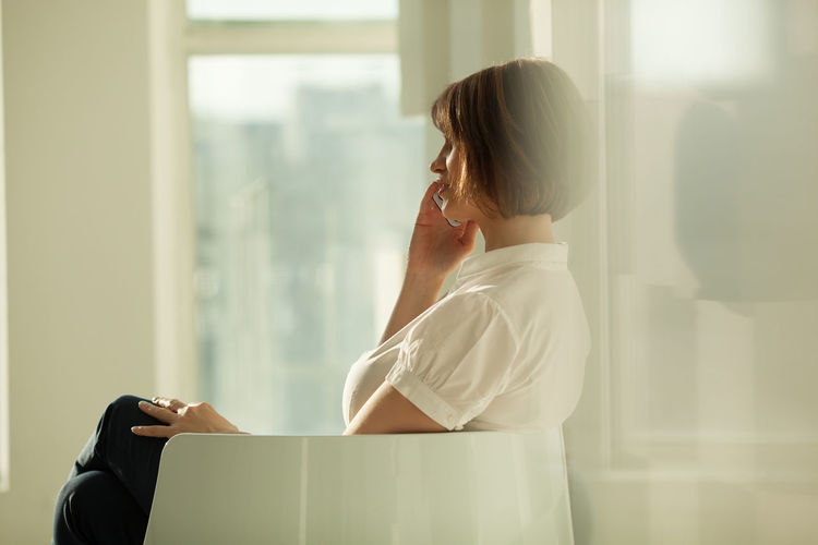 Side view of businesswoman using smart phone while sitting on chair