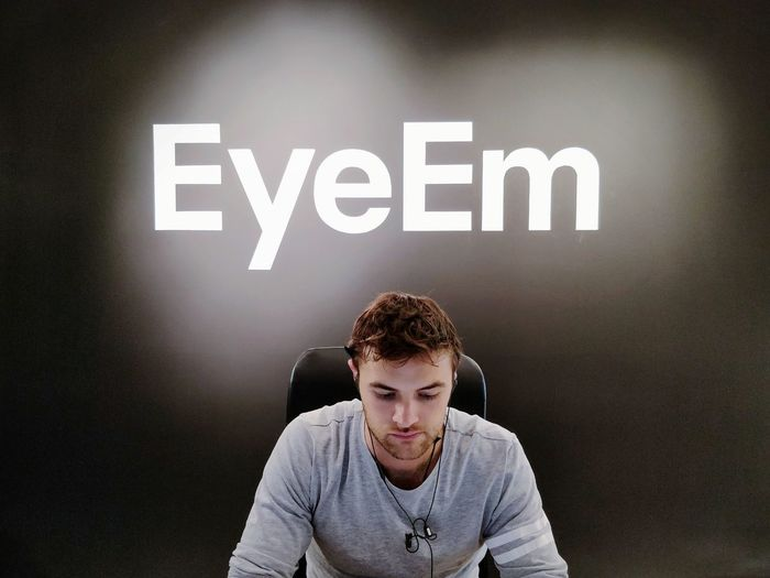 Welcome to EyeEm, how may I help you? Front Desk Ryan Logo Fresh Paint Portrait Sitting Front View Western Script