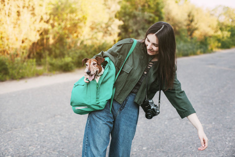 A smiling girl with a camera around her neck holds a green backpack on her shoulder.