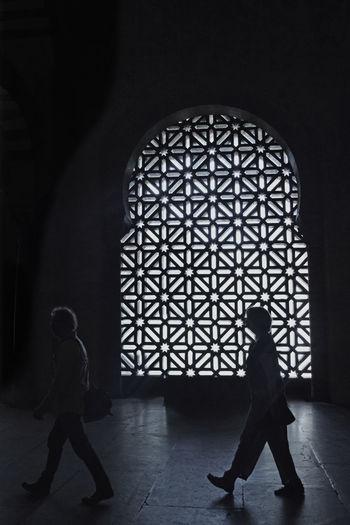 Rear view of silhouette people walking on floor in building