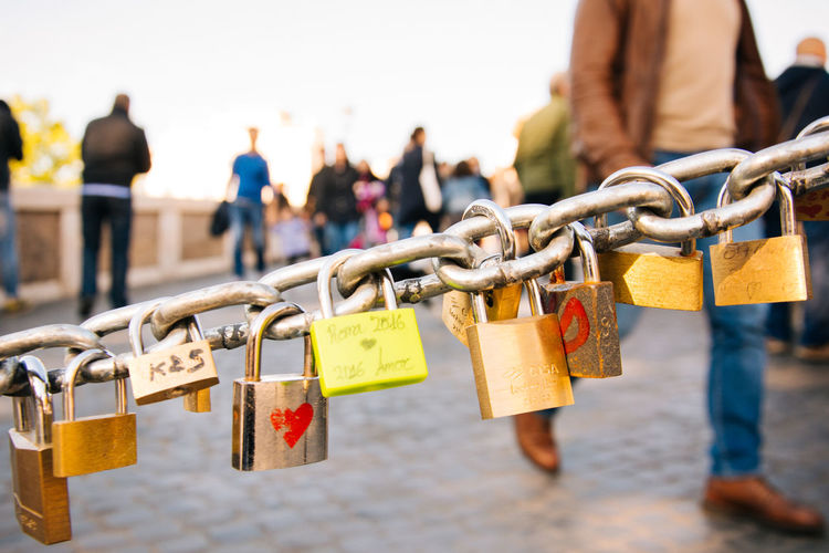 Close-Up Of Padlocks Hanging On Chain Against Blurred People