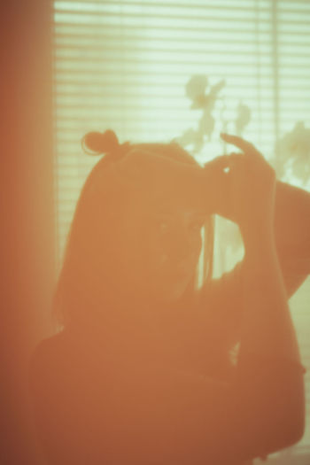 Rear view of silhouette woman holding window