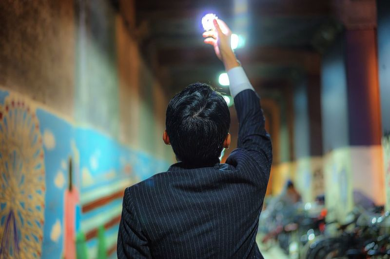 Rear View Of Man Holding Illuminated Lighting Equipment In City At Night