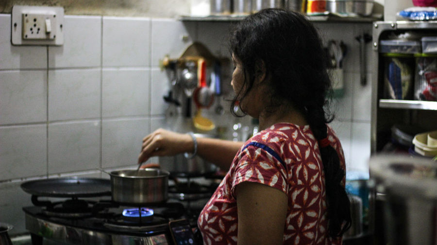 Woman preparing food while standing in kitchen at home