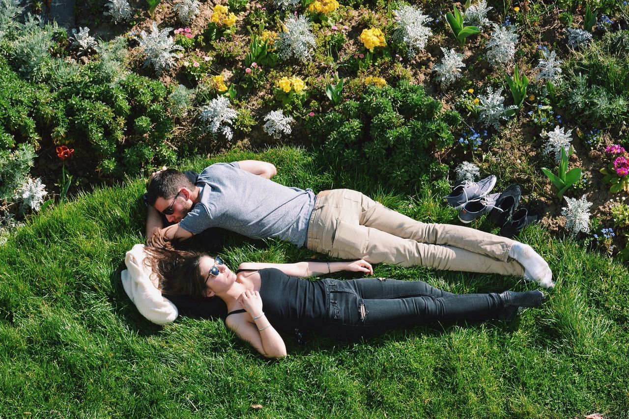 YOUNG COUPLE LYING ON FIELD