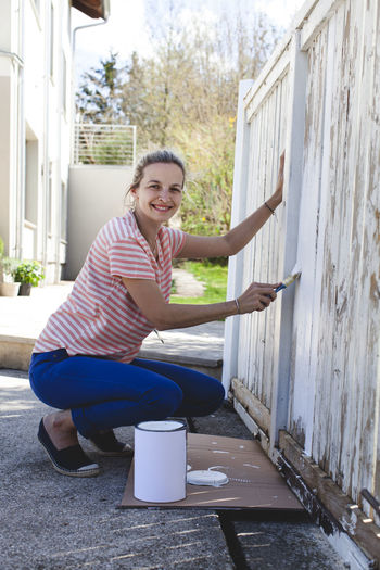 Portrait of smiling woman painting fence at yard