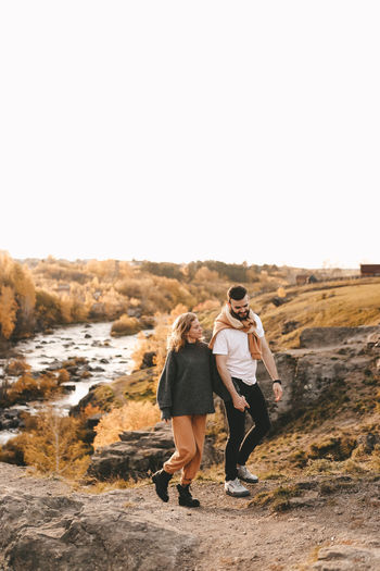 A happy couple in love a man and a woman are traveling walking hiking in the autumn forest in nature