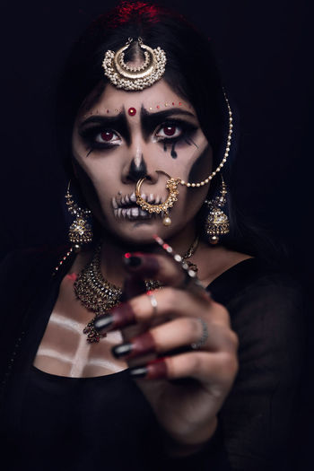 Close-up of young woman in traditional clothing with spooky make-up against black background