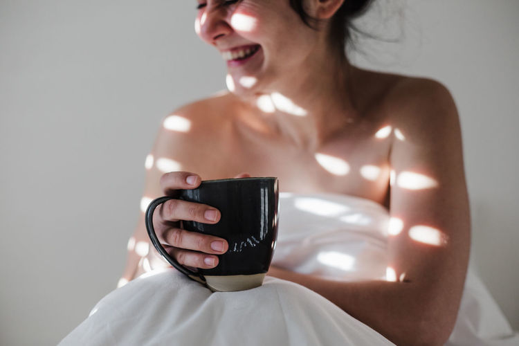 Portrait of shirtless woman holding camera