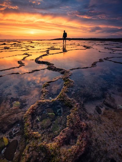 Man standing at frozen sea against sky during sunset