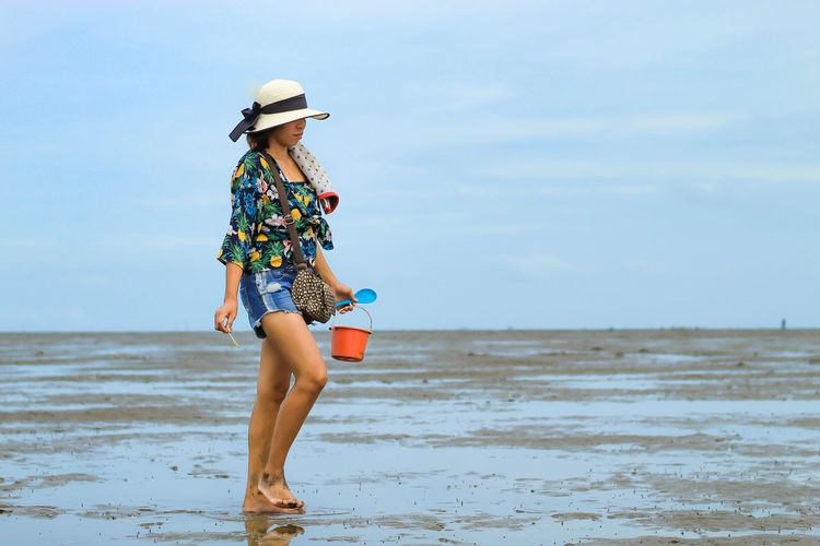 Full Length Of Woman Holding Bucket At Beach