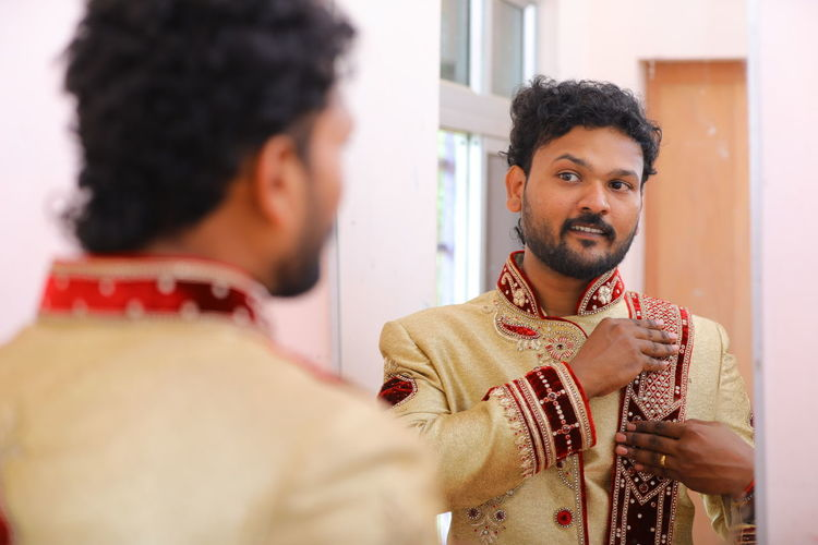 Happy young man with traditional clothing looking at mirror while standing at home
