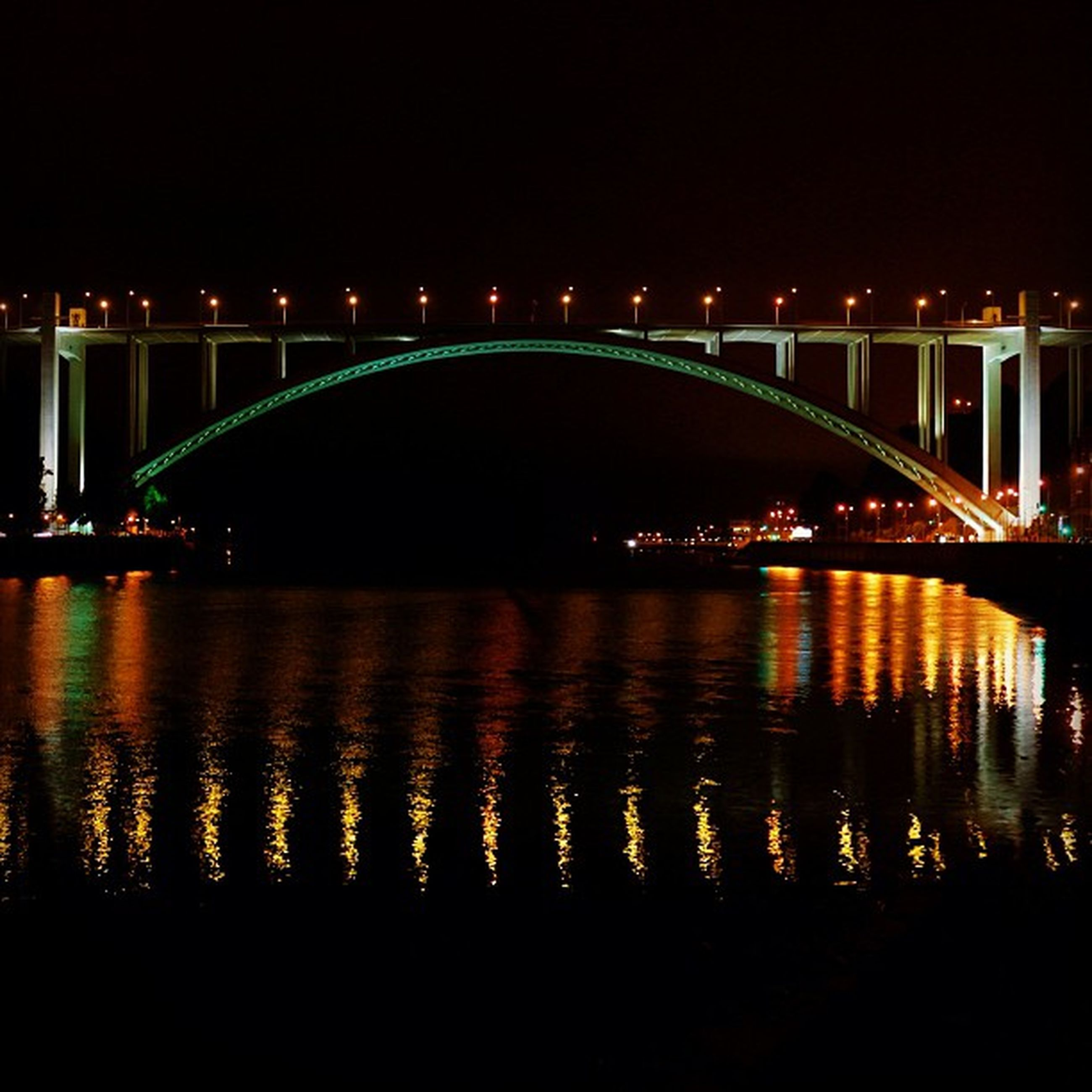 illuminated, night, water, reflection, bridge - man made structure, connection, river, bridge, built structure, architecture, street light, waterfront, lighting equipment, arch bridge, outdoors, dark, engineering, tranquility, arch, no people