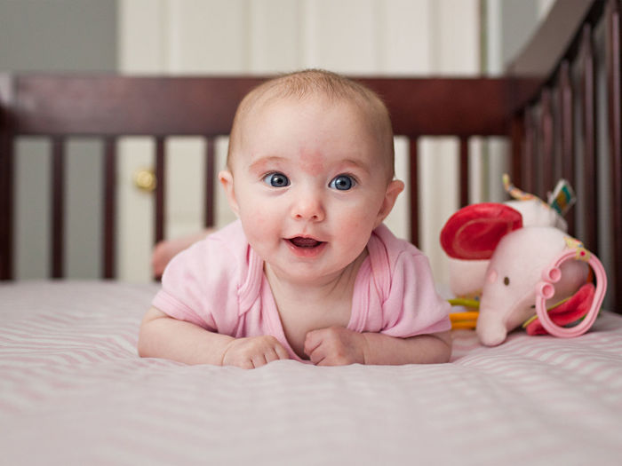 Close-Up Of Cute Baby Girl Smiling On Crib
