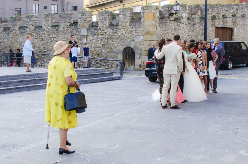 Bride and wedding party outside the church in Gijon Asturias, Spain. City Life City Street Dress Groom Taking Photos Wedding Architecture Bride Building Exterior Built Structure City Editorial  Full Length Large Group Of People Leisure Activity Lifestyles Outdoors People Real People Travel Destinations Wedding Day Wedding Dress Wedding Party Women Yellow