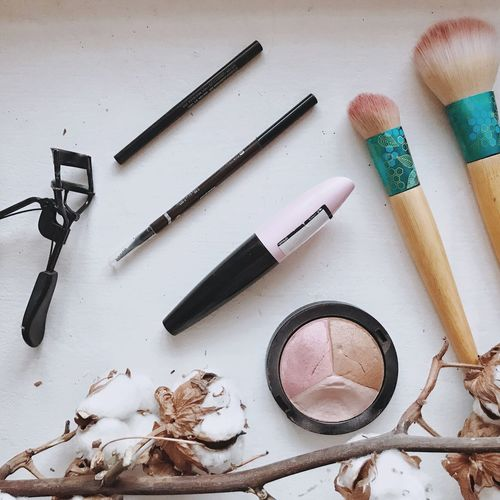 High angle view of beauty products by dried cotton plant on table