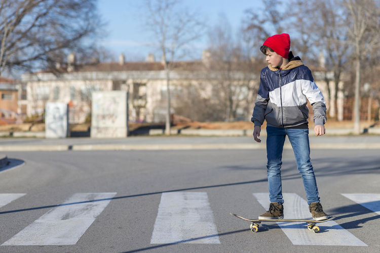 Hat Jeans Skateboarding Sunlight Activity Boy Boys Building Exterior Day Enjoyment Full Length Lifestyles Male Nature One Person Outdoors People Real People Skateboard Sport Streetphotography Sunrise Teenager Tree Warm Clothing