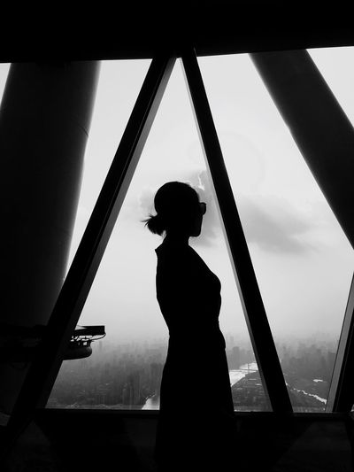 Silhouette woman standing by window against sky