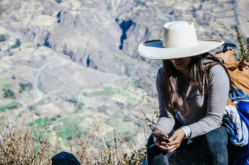 Woman using mobile phone while sitting on mountain