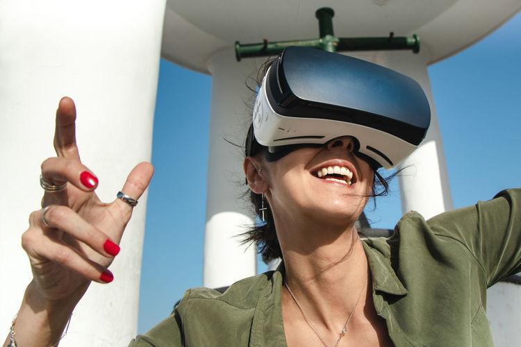 Laughing woman wearing virtual reality simulator outdoors