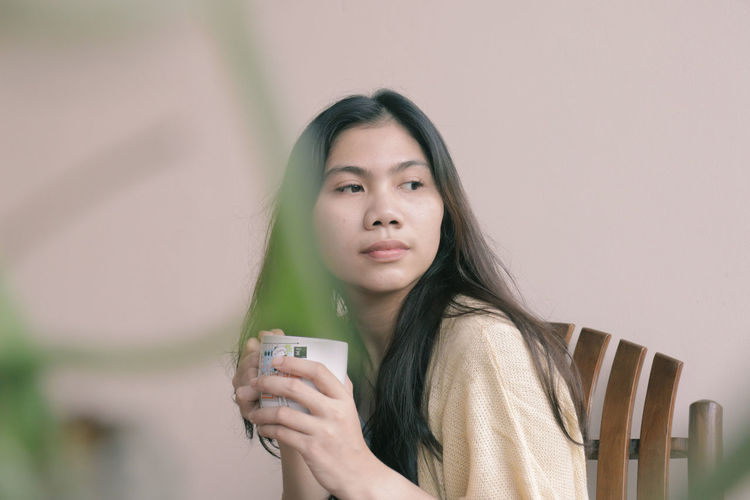 Portrait of young woman drinking glass against wall