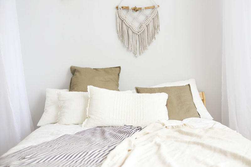 White curtain on bed against wall at home