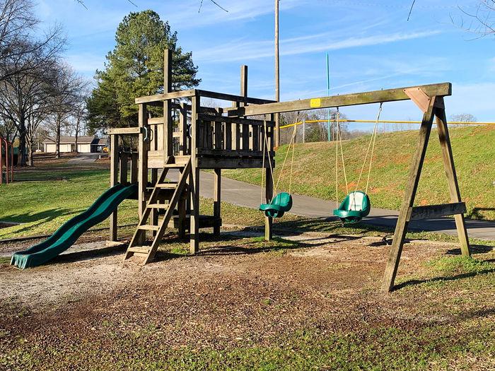 Empty swing in park against sky