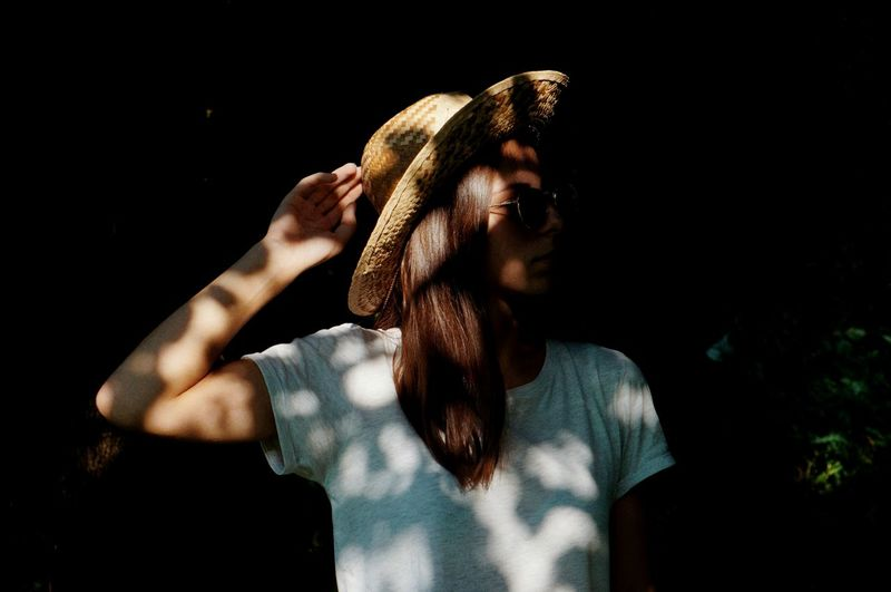 Close-up of young woman holding straw hat in dark