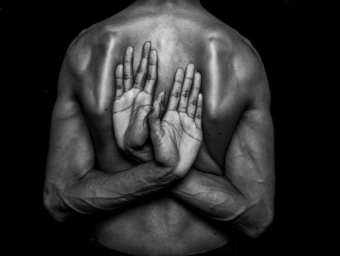 Rear view of man standing with hands behind back