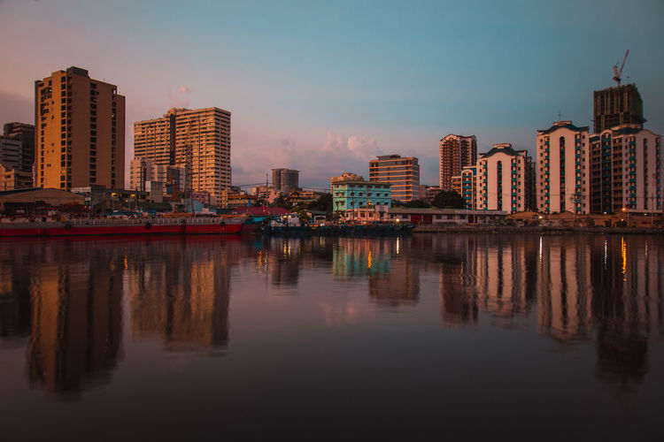 Reflection of illuminated buildings in the city against the pasig river on a sunset.