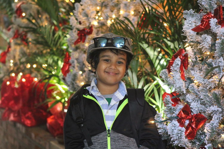 Portrait Of Smiling Boy Against Christmas Tree