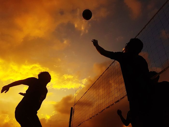 Low angle view of silhouette man playing with ball against sky during sunset