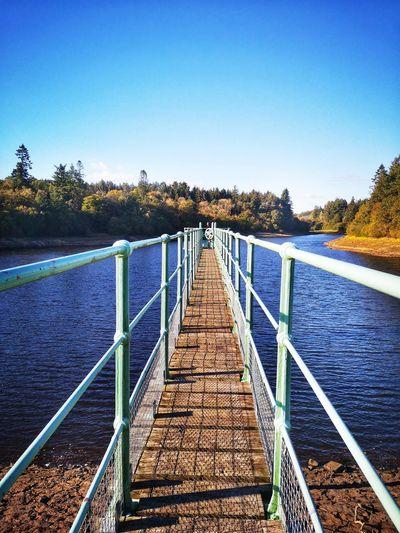 Bridge over calm blue sea against clear sky