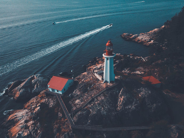 High angle view of lighthouse by sea and buildings