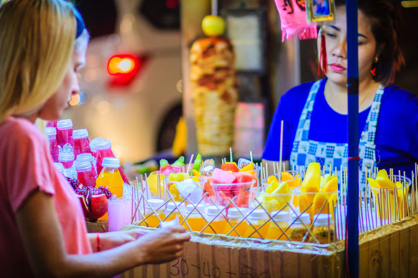 Bangkok, Thailand - March 2, 2017: Unidentified tourist is buying sliced fruits that arranged in plastic cup from street food vendor at Khao San Road night market, Bangkok, Thailand. Khao San Rd Khao San Road KhaoSan Khaosan Rd. Khaosandroad Adult Cake Celebration Child Event Females Food Food And Drink Freshness Girls Group Of People Indoors  Khao San Khao San Knok Wua Khao San Rd. Khaosan Road Khaosanroad Leisure Activity Lifestyles Night Market Night Market In Thailand People Real People Selective Focus Sweet Food Temptation Togetherness Women