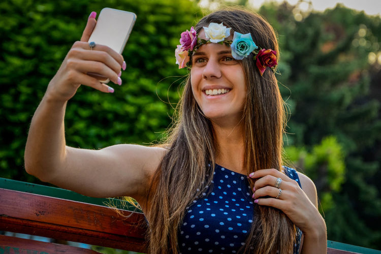 Happy woman taking selfie while sitting on bench at park