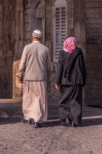 Two arabic men walking Middle East Palestine Adult Building Exterior Israel Men Outdoors Palestinian Real People Rear View Senior Adult Togetherness Traditional Clothing Two People