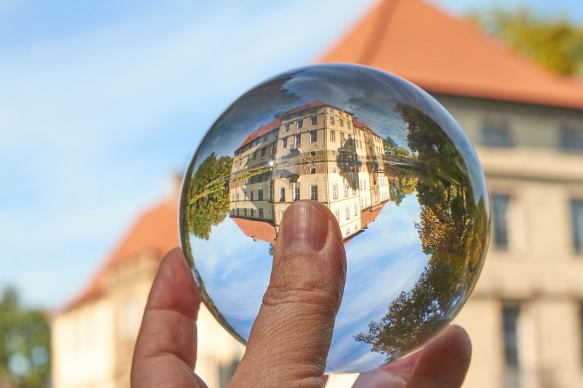 Water Castle Castle Architecture Ball Building Building Exterior Built Structure Close-up Crystal Ball Day Finger Focus On Foreground Glass Glass - Material Hand Holding Human Body Part Human Hand Magic Nature One Person Outdoors Real People Reflection Sky Sphere Upside Down Water Water Castle