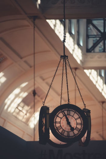 Close-up of clock hanging on ceiling
