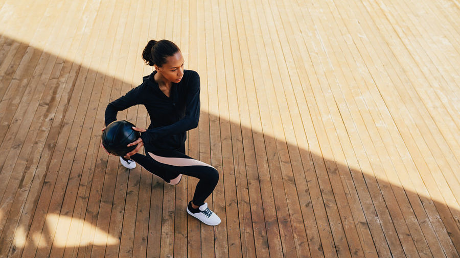 Full Length Of Woman Exercising With Ball On Boardwalk During Sunny Day