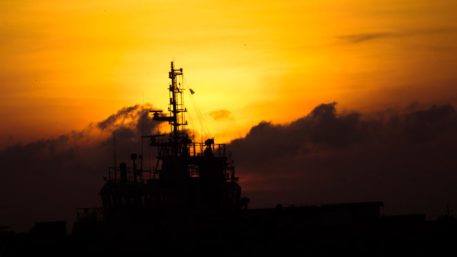 Silhouette Ship By Sea Against Sky During Sunset