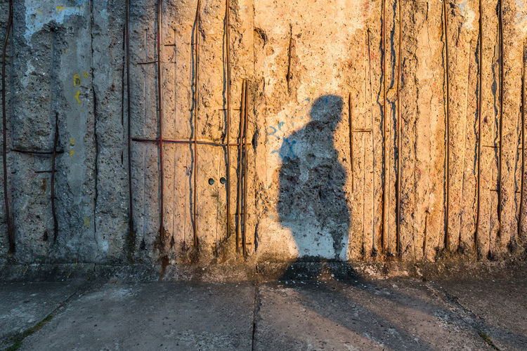Shadow of man on damaged wall