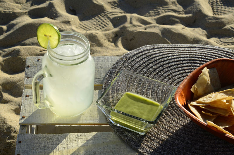 Lemonade with lime slice, green salsa and tortilla chips afternoon snack at the beach